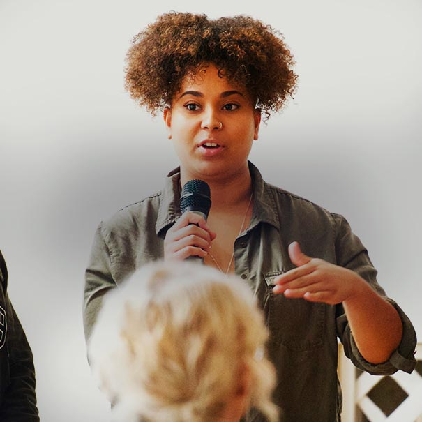 Young woman holds a microphone whilst speaking to a group